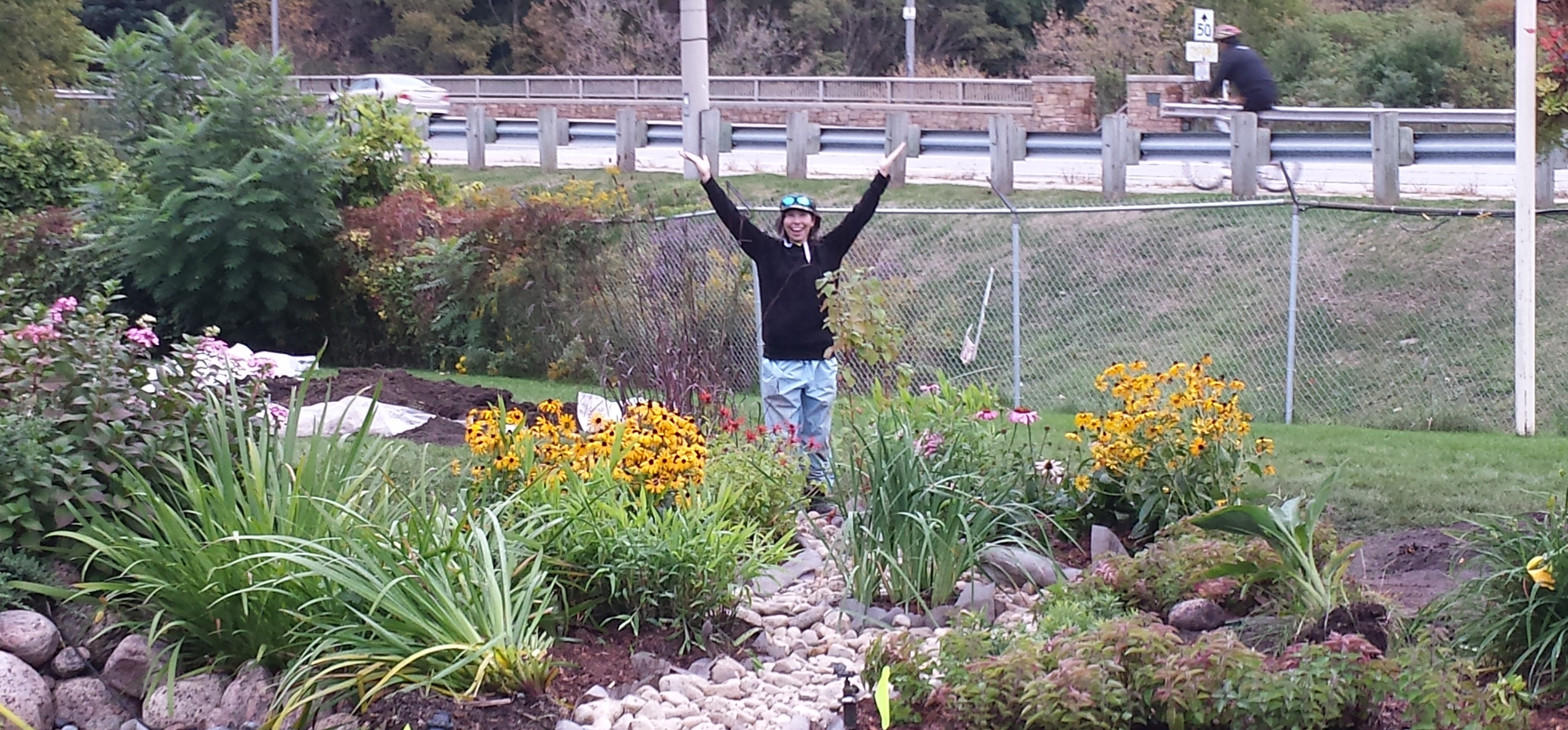 Volunteer posing with the completed rain garden.